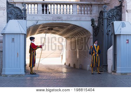 VATICAN CITY VATICAN - OCTOBER 16 2016: Famous Swiss Guard guarding the entrance to the Vatican City. The Papal Guard with about 100 men is the world's smallest army.