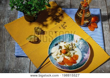 Cold and tasty vanilla ice cream with physalis, pumpkin seeds, and dried apricots on a yellow fabric and on a wooden background. A little tea spoon near the dessert, top view. A beverage on a striped cloth.