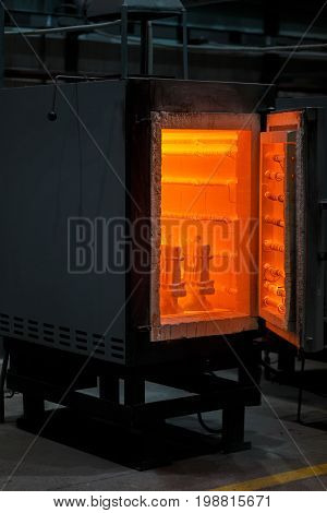 A big furnace on a dark black industrial background. An opened heated oven for melting. Pressuring equipment and constructions. Metallurgical production business.