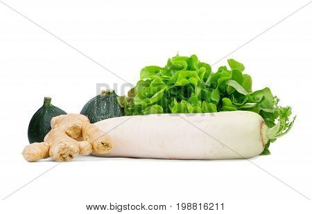 A close-up of black zucchinis next to green salad leaves, white turnip and ginger root isolated on a white background. Organic autumn vegetables full of vitamins. Natural ingredients for salads.