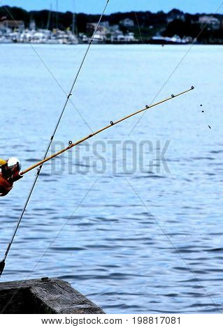 Fishing on waterfront pier using fishing rods and reels outdoors.