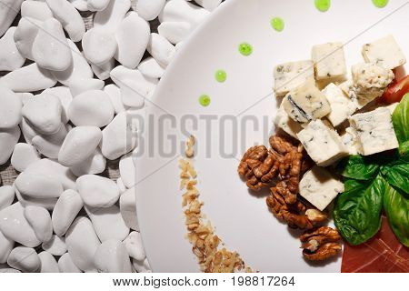 A top view of of Roquefort cheese, crunchy walnuts, fresh basil leaves and sliced meat on a plate on a white rocks background. Restaurant delicacy and expensive appetizers concept.