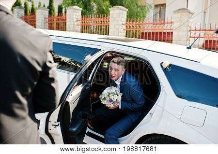 Portrait Of A Handsome Groom Coming Out Of The Wedding Limousine.