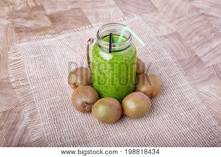 Healthy green smoothie made from kiwi on a white tablecloth on a light wooden background. A mason jar full of sweet beverage with colorful straws on a desk. Many whole kiwi around a drink.