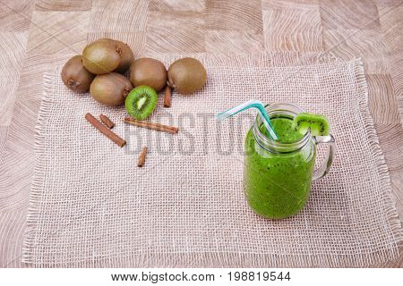 Top view of a mason jar full of organic drink from ripe kiwi with a colorful straw and slice of fruit on a top on a wooden background. A heap of whole and cut kiwi and cinnamon on a white tablecloth.