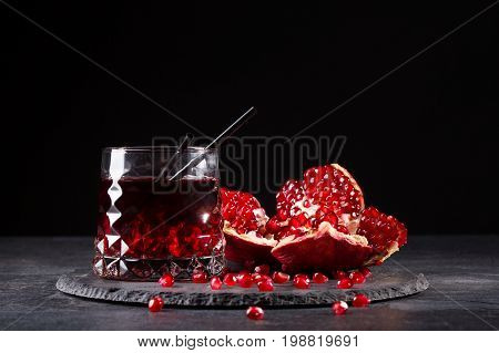 A transparent glass of healthy pomegranate juice and a cut garnet on a round plate on a saturated black background. Organic summer fruity red cocktail with straws and fresh garnet.