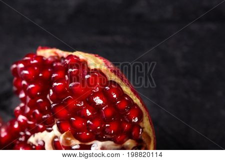 Useful red garnet berries for desserts or drinks used on a dark gray background. Macro photo of ripe bright red pomegranate cut into pieces. Beneficially and nutritious vitamins.