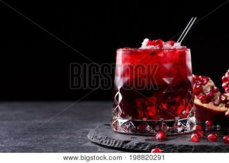 Close-up of a transparent glass of sweet pomegranate juice with ice and a cut garnet on a round plate on a saturated black background. Healthful and fruity red cocktail with straws and fresh garnet.