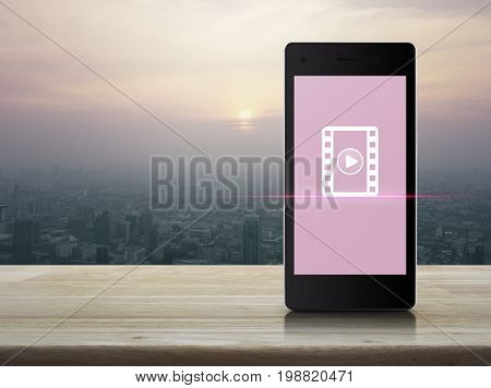 Play button with movie icon on modern smart phone screen on wooden table over city tower at sunset vintage style Cinema online concept