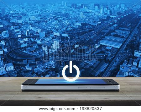 Power button icon on modern smart phone screen on wooden table over city tower street and expressway Start up business concept