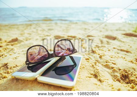 two phones on the beach with sunglasses in sunny day