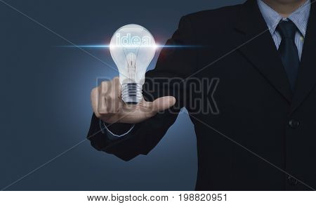 Businessman pointing to light bulb with blue spot light on blue background Business start up idea concept