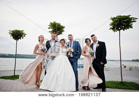Amazing Wedding Couple And Crazy Groomsmen With Bridesmaids Having Fun On The Lakeside.
