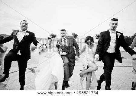 Amazing Wedding Couple And Crazy Groomsmen With Bridesmaids Having Fun On The Lakeside.  Black And W