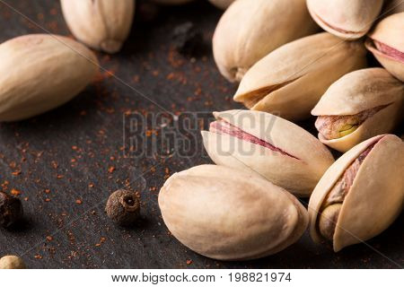 Close-up of a heap of crunchy pistachios and spicy pepper on a black table background. Traditional restaurant ingredients. Salted pistachio nuts for a party or celebration.