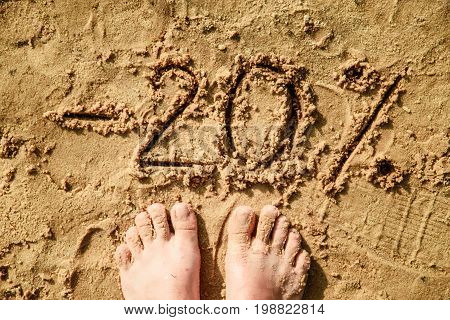 20 lettering written on sand. Summer beach background