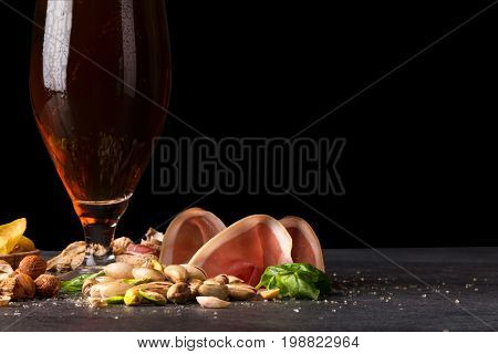 An alcoholic drink and appetizers on a black stone background. Sliced red jamon and pistachio nuts next to a tall pint of golden ale. Celebration and party concept. Copy space.