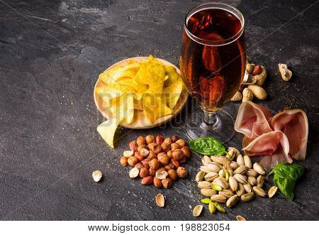 A view from above on different tasteful snacks and a tall glass of dark beer on a gray table background. A plate of nachos, crunchy nuts, basil leaves and cut prosciutto. Delicious refreshing beer.