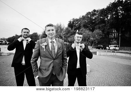Groom With His Groomsmen Going Wild On His Wedding Day On The Lakeside. Black And White Photo.