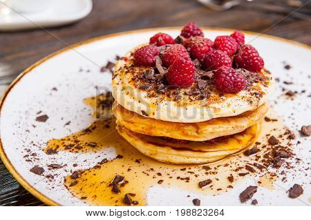Delicious Pancakes With Fresh Raspberry, Chocolate Crumbs And Maple Syrup On The White Round Plate O