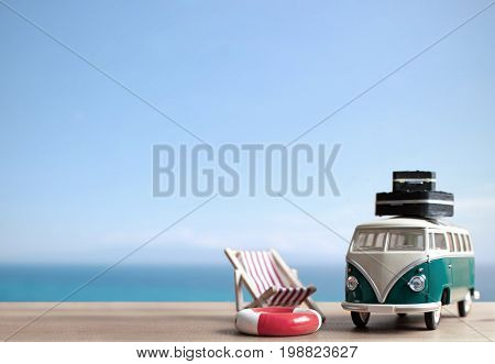 Miniature motor home with deck chair and luggage and space for text