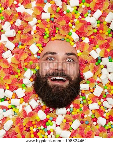 From above view of bearded man looking excitedly at camera while lying in sweets and candies.