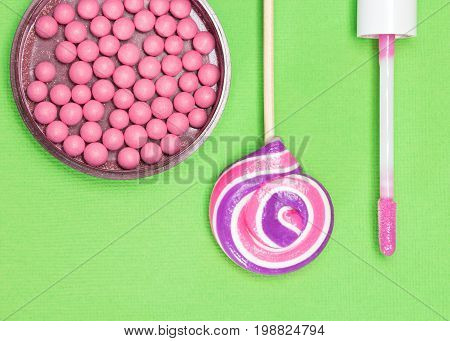 Makeup set in pink color. Basic make up products for creating natural fresh look: blush and lip gloss on green background with lollipop