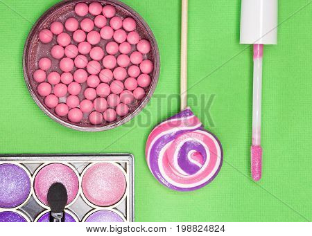 Pink and purple make up products: blush, lip gloss and eyeshadow with lollipop. Harmonious color combination in makeup