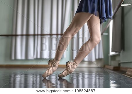 Legs of a ballet dancer in a blue dance wear who stands on pointes next to the ballet barre. She wears beige pointe shoes. Her feet reflected in the glossy floor. Closeup. Horizontal.