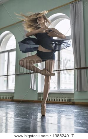 Young ballerina is posing in a motion in the ballet hall opposite large arch windows. She is circling on the left leg. Girl wears a dark dance wear and beige poine shoes. Vertical.