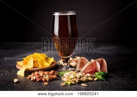 A glass of dark beer with nutritious peanuts and pistachios, tasteful jamon and nachos in a plate. Appetizing and cold beer with foam. Brewery, cuisine, restaurant business concept. Copy space.