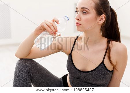 Young sport woman drinking water. Confident fitness girl holding plastic bottle, thirsty after training, healthy lifestyle concept