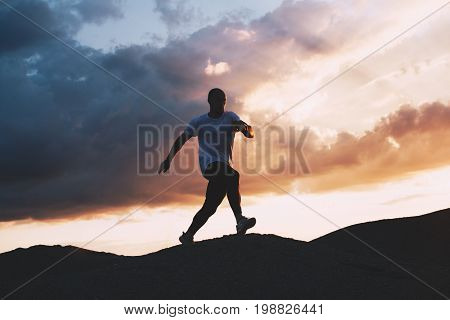 Muscular athlete is engaged in fitness and jogging on nature. Jogging on outdoor at background of sunset