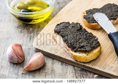 Black olive tapenade with anchovies, garlic and olive oil on wooden table