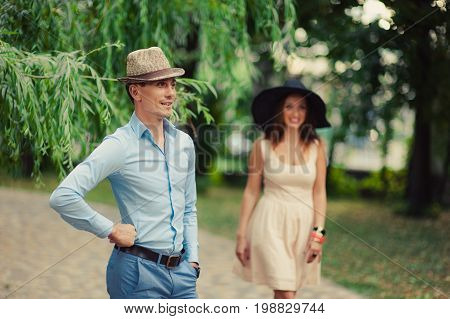 Girl In A Hat With Wide Brim And A Guy On A Walk In The Park