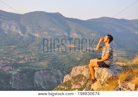 Young man sits on a cliff edge on the top of mountain with gorgeous view and eats. Dangerous Place. Adrenaline. Hiker on the top