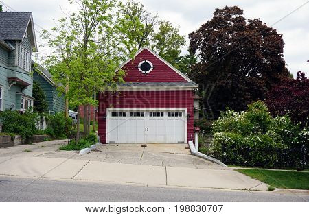 A red garage with a white door in the Courthouse Hill Historic District of Cadillac, Michigan.