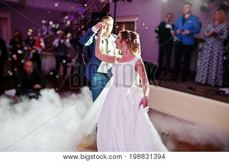 Newly Married Couple Dancing On Their Wedding Party With Heavy Smoke And Multicolored Lights On The