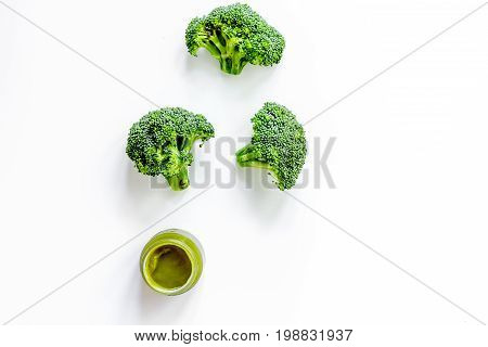 Broccoli puree for baby on white background top view.