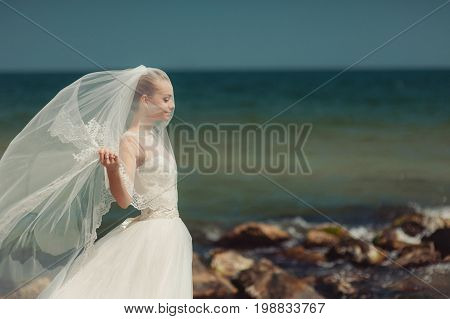 Bride Veiled By A Veil For A Walk By The Sea