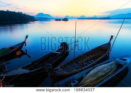 Beautiful sunrise landscape view of fisherman and wooden boat in early morming at Samchong-tai fishing village in Phang-NgaThailand