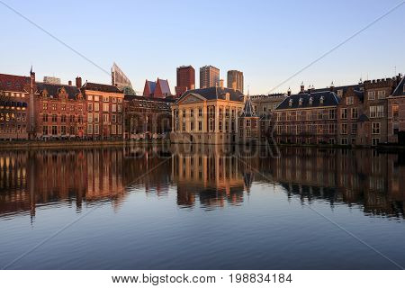 Historic architecture of the Hague seat of government like government building the tower in which the prime minister holds office and Mauritshuis museum with modern buildings in the background with reflection in the water of Hofvijver lake in the Netherla