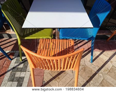 Multicolored plastic table and chairs. Restaurant furniture in the open sun. Minimalistic composition, laconic, bright shades