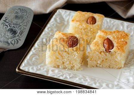 Basbousa (namoora) traditional arabic semolina cake with almond and syrup. Dark background. Copy space