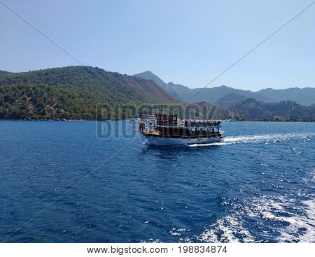 Sea, sky, boat, summer, sunny day, yacht near picturesque hilly coast. Blue and gree pure natural colors. The concept of  water trips