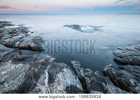 Tranquil minimalist landscape of stony coast with gray rocks and calm water under blue sky in twilight in early morning simple beautiful calm natural background