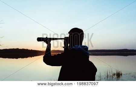 Guy with a telescope on nature sunset sun