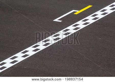 Minimalistic photo of a chequered finish line on a track. Signifies the end of a project or event