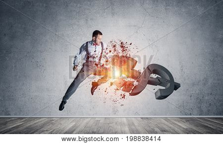 Young furious businessman jumping and crashing with kick stone dollar symbol