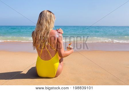 Young woman sits on beach smearing sunscreen on skin